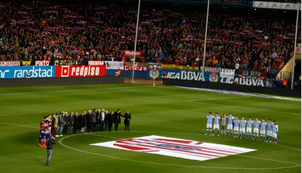 Jugadores y veteranos del equipo abrazados junto a la camiseta gigante con el 8 de Luis./Foto:ATM